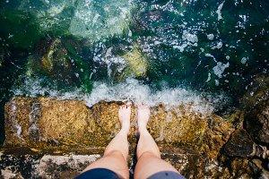 Female feet in clear blue water