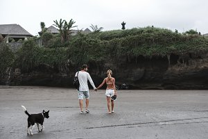 Young couple walking with dog