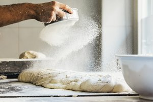 Baker spreading flour to dough.