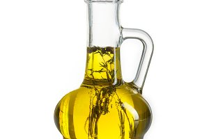 Olive oil in bottle with herbs isolated on white background