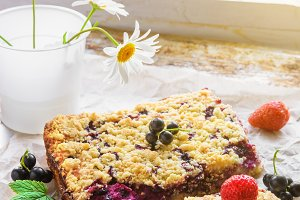 Black currant, strawberry and cottage crumble cake on baking paper and rustic background