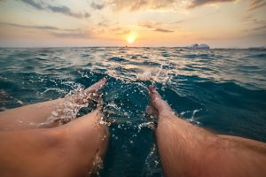 Image of legs of two people splashing aquamarine sea water on sunset