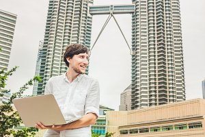 BANNER Man businessman or student in casual dress using laptop in a tropical park on the background of skyscrapers. Mobile Office concept Long Format