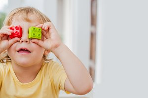 BANNER The boy makes eyes of colorful children's blocks. Cute little kid boy with glasses playing with lots of colorful plastic blocks indoor. Promotion of skills and creativity Long Format