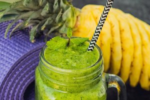BANNER Green smoothies made of spinach and pineapple and a yoga mat. Healthy eating and sports concept Long Format