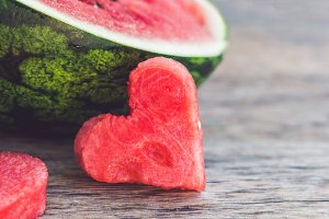 BANNER Healthy watermelon smoothie with mint, a piece of watermelon, hearts and a striped straw on a wood background Long Format