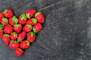 BANNER Fresh strawberries array heart shape on old wooden background Long Format