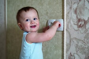Little baby playing with plug.