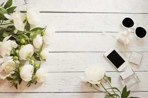 Bouquet of white peonies, phone and a bottle of perfume on the wooden table