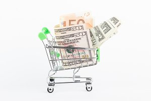 American dollars and fifty euro in the shopping push cart, isolated