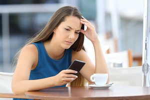 Worried woman watching phone
