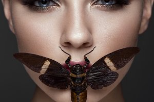 Portrait of beautiful girl with colorful make-up and cicada. Beauty face.