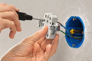 hands installing electrical socket