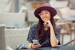 Smiling young woman with smart phone in cafe shop
