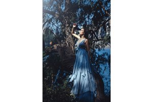 Beautiful woman in blue dress in fairy forest.