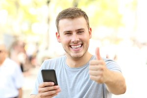 Man with thumbs up holding phone