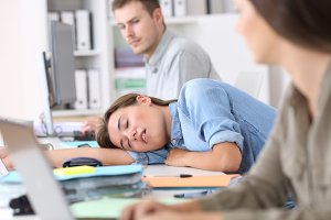 Fatigued employee sleeping on a desk