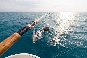 Fisherman fishing rod on the sunset closeup