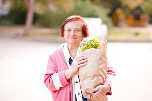 Happy old woman with food