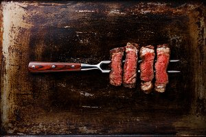 Slices of steak Rib eye on fork