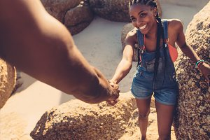 Man helping woman climbing rock