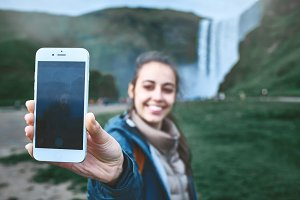 smiling woman making selfie on a Skogafoss waterfall background