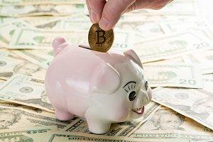 Hand placing bitcoin coin into piggy bank