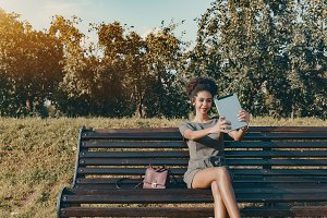 Black girl on park bench with pad