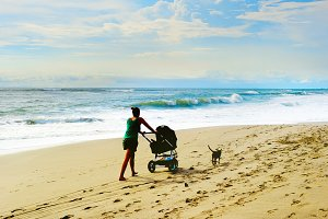 Woman with baby carriage at beach
