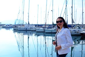 Woman dressed in nautical style in yacht marina