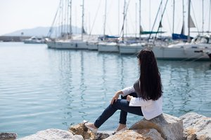 woman dressed in nautical style sitting by seaside in yacht mari