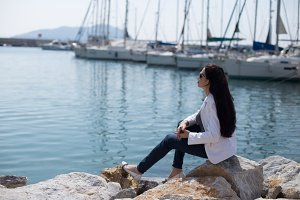 woman dressed in nautical style sitting by seaside