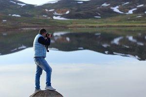 Landscape photographer photographing mountain lake