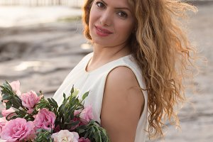 Beautiful woman in white dress holding bouqet of pink lisianthus