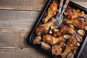 Oven baked chicken legs with onions, garlic and peppers on a dark wooden background closeup. Top view with copy space. Wooden rustic table