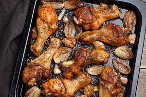 Oven baked chicken legs with onions, garlic and a mixture of peppers on dark wooden background closeup. Top view
