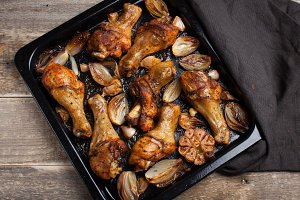 Oven-baked chicken leg quarters with onion, garlic and capsicum on a dark background closeup. Top view