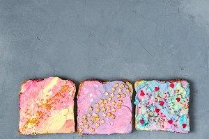 Three Unicorn Toasts on a gray concrete texture background