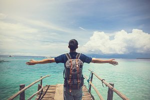 Traveling male backpacker spreading arms in tropical island with carefree and relaxing attitude - vacation concept