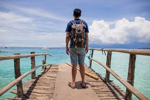 Traveling man with backpack looking out towards the beautiful and crystal clear ocean sea in summer