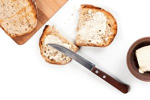 Fresh wholemeal homemade rural bread on a wooden cutting desk with butter