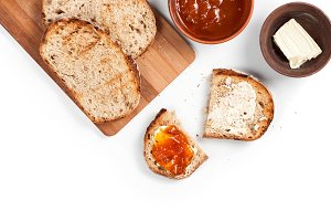 Morning breakfast table with fresh wholemeal homemade rural bread on a wooden cutting desk, apricot jam and butter