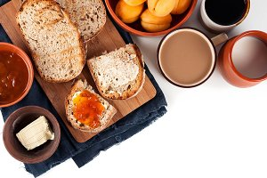 Morning breakfast table with fresh wholemeal homemade rural bread on a wooden cutting desk, jam, butter, apricots, coffee and milk