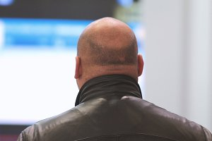 Big bald man in leather jacket at conference hall - rear view