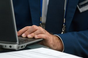 Businessman working on a laptop at conference - close up