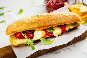 Sandwich with dried tomatoes, brie cheese and rocket salad