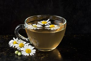 Cup of organic, anti-inflammatory, antimicrobial herbal tea with fresh chamomile flowers