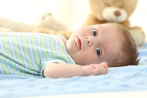 Baby lying on a bed looking at you