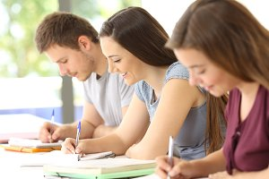 Three students taking notes