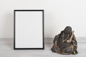 Photo frames next to Buddha figure on wooden table. Decor.